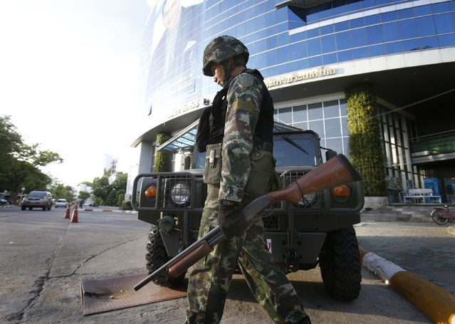 A Thai soldier walks in front of the National Broadcasting Services of Thailand television station in Bangkok May 20, 2014. Thailand's army declared martial law on Tuesday to restore order after six months of anti-government protests which have left the country without a functioning government.The declaration did not constitute a coup and was made in response to deteriorating security, an army general said. (Photo by Athit Perawongmetha/Reuters)