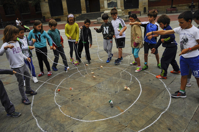 In this Tuesday, June 16, 2015 photo, a group of children play with their spinning tops outside of their National College in Pamplona, northern Spain. After many years forgotten, the Spanish children are returning to games played in years gone by. (Photo by Alvaro Barrientos/AP Photo)
