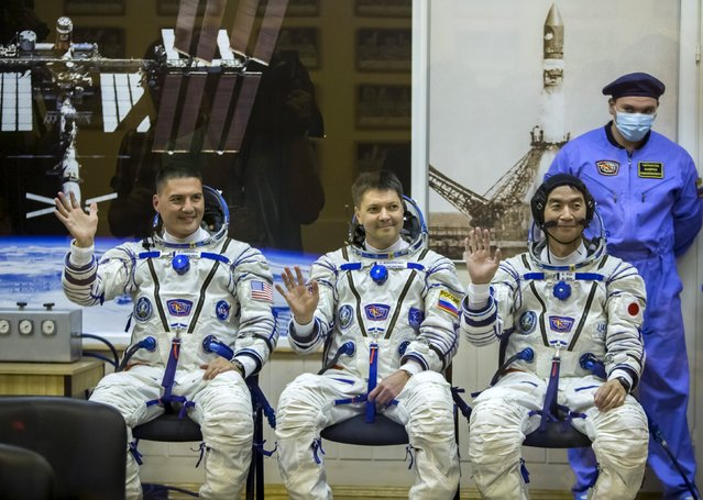 The International Space Station (ISS) crew members (L to R) Kjell Lindgren of the U.S., Oleg Kononenko of Russia and Kimiya Yui of Japan wave after donning space suits at the Baikonur cosmodrome, Kazakhstan, July 22, 2015. (Photo by Shamil Zhumatov/Reuters)