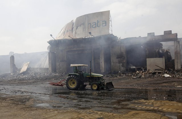 A tractor runs past a damaged building on the tarmac of Jinnah International Airport, after Sunday's attack by Taliban militants, in Karachi June 10, 2014. REUTERS/Athar Hussain