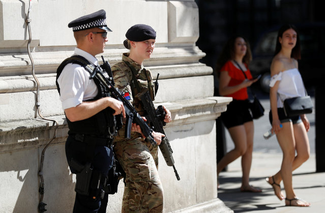 Tourists walk past a soldier and an armed police officer on duty on Whitehall in London, Britain, May 26, 2017. (Photo by Peter Nicholls/Reuters)