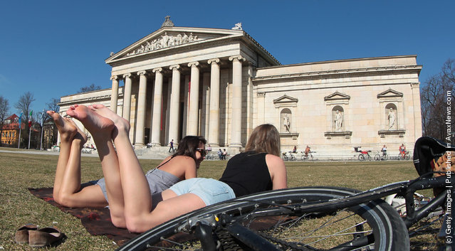 Young girls are taking a sunbath in front of Glyptothek, museum for Greek and Roman art on March 17, 2012 in Muenchen, Germany