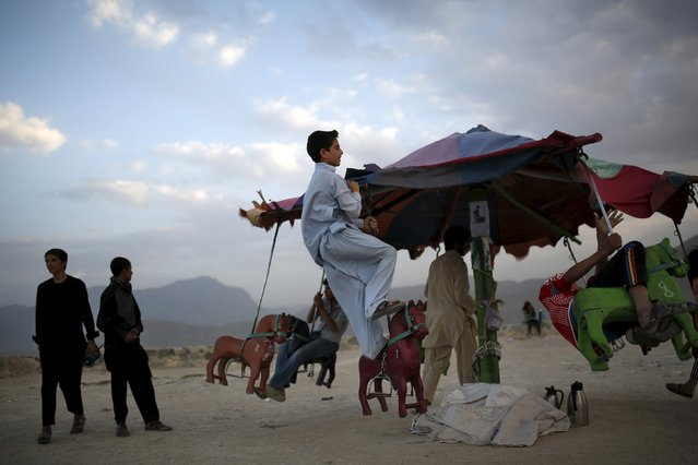 An Afghan boy plays on a merry-go-round on a hill top in Kabul July 20, 2015. (Photo by Ahmad Masood/Reuters)