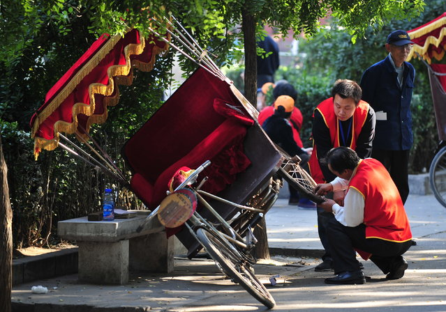 A driver repairs the wheel of his pedicab while awaiting his customer base of mostly tourists in Beijing on October 19, 2008. China's economic growth slowed to 9.9 percent in the first three quarters of the year, the government said on October 20, 2008, adding that the global slowdown was starting to have an impact. The third quarter figure marked a weakening from 10.4 percent in the first half of 2008, and 12.2 percent in the first three quarters of 2007, according to earlier data published by the bureau. (Photo by Frederic J. Brown/AFP Photo)