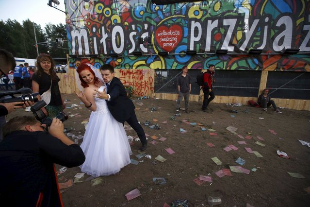 A newly married couple poses during a photo session near the main stage at the 21st Woodstock Festival in Kostrzyn-upon-Odra, Poland July 30, 2015. An estimated 200,000 people attended the ongoing festival, a brainchild of Polish journalist and social campaigner Jerzy Owsiak, on Friday. Owsiak initiated the event to say thank you to those who donated money to his GOCC charity organisation that delivers medical care for children. (Photo by Kacper Pempel/Reuters)