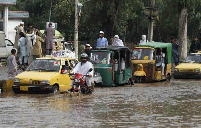 Vehicles are seen at a flooded street after heavy rainfall in Peshawar, Pakistan, July 27, 2015. Flash flooding caused by torrential monsoon rains has killed at least 28 in Pakistan and affected hundreds of thousands of people, according to aid agencies, with further downpours expected in the coming days. (Photo by Fayaz Aziz/Reuters)