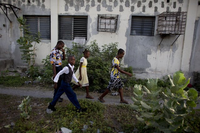 In this June 27, 2015 photo, Johnly Clif Gaspard, back left, heads to Sunday morning Mass with his mother and two younger siblings, as they leave the abandoned shipping depot where they live in Port-au-Prince, Haiti. Although his mother works full-time in a button factory and Gaspard earns money selling motorized toys built from scrap materials, the family cannot afford to move out of the depot where they are squatting along with five other families. (Photo by Rebecca Blackwell/AP Photo)