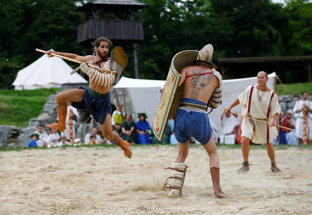 "Members of the ""Familia Gladiatoria Carnuntina"" fight in the historic amphitheatre during the Roman Festival at the archeological site of Carnuntum in Petronell, Austria, June 11, 2016. (Photo by Leonhard Foeger/Reuters)"