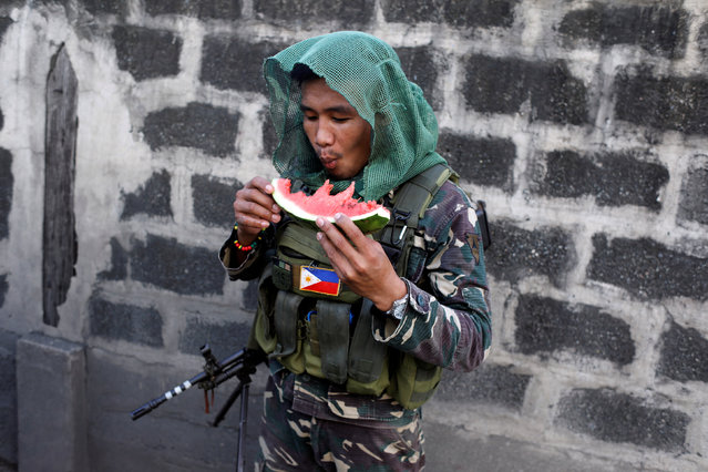 A Philippine army soldier eats a watermelon while patrolling in Iligan, as government forces continue their assault against insurgents from the Maute group, who have taken over large parts of Marawi City, Philippines June 24, 2017. (Photo by Jorge Silva/Reuters)