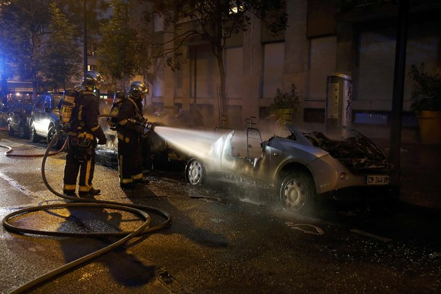 French firemen spray water to extinguish two Autolib' electric cars that were set on fire on a street at the end of a day of nationwide protests against plans to reform French labour laws in Paris, France, June 14, 2016. (Photo by Jacky Naegelen/Reuters)