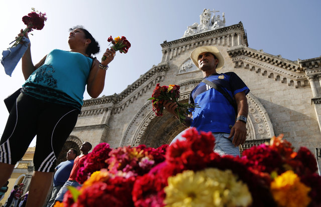 Vendors sell flowers at the entrance of the Colon cemetery during Mother's Day in Havana, Cuba, Sunday, May 10, 2015. (Photo by Desmond Boylan/AP Photo)