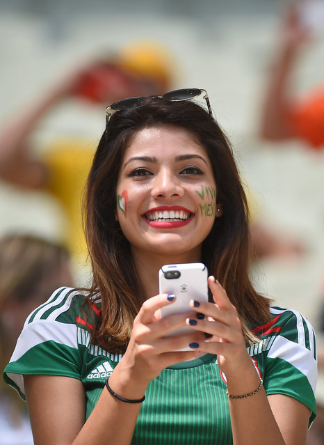 A Mexican supporter takes a photograph as she cheers for her team ahead of the Round of 16 football match between Netherlands and Mexico at Castelao Stadium in Fortaleza during the 2014 FIFA World Cup on June 29, 2014. (Photo by Emmanuel Dunand/AFP Photo)