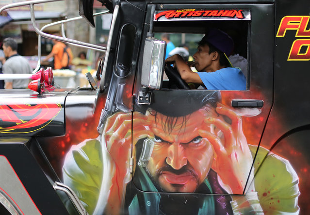 A Filipino jeepney driver waits for passengers during traffic in suburban Quezon City, north of Manila, Philippines on Tuesday, July 8, 2014. Passenger jeepneys are popular means of public transportation in the country. They come in various colors and are sometimes decorated with paintings of religious icons, popular artists and comic characters. (Photo by Aaron Favila/AP Photo)