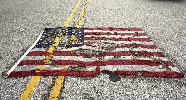 A partially burned American flag lies on the street near the spot where Michael Brown was killed before an event to mark the one year anniversary of his killing in Ferguson, Missouri August 9, 2015. (Photo by Rick Wilking/Reuters)