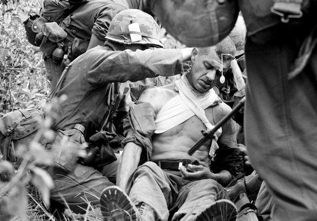 In this Jan. 16, 1966 file photo taken by Associated Press photographer Horst Faas, Lt. Col. George Eyster of Florida is placed on a stretcher after being shot by a Viet Cong sniper at Trung Lap, South Vietnam