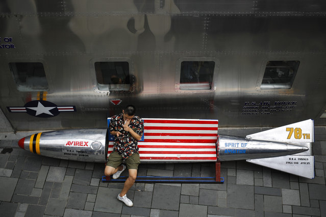"In this July 20, 2017 file photo, a man lights a cigarette on a bench in a shape of a mocked aerial bomb and a U.S. flag outside a fashion boutique selling U.S. brand clothing at a mall in Beijing. U.S. Treasury Secretary Steve Mnuchin says the Chinese government's ""intervention in its economy"" is to blame for China's trade surplus with the United States. But economists say while Beijing hampers market access, the bulk of the surplus is due to China's role as final assembly point for components from other countries, for which it keeps a fraction of the revenue. (Photo by Andy Wong/AP Photo)"