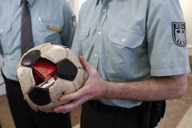 A German customs officer holds a confiscated soccer ball used as a hiding spot to smuggle cigarettes to Germany at the Finance ministry in Berlin March 11, 2011. (Photo by Fabrizio Bensch/Reuters)