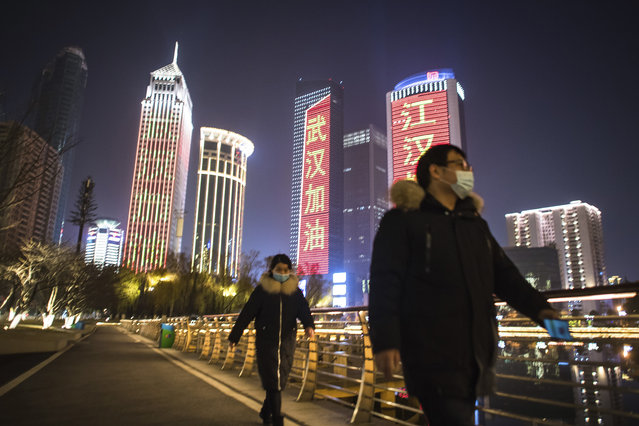In this Friday, January 31, 2020, photo released by China's Xinhua News Agency, people wearing face masks walk past buildings lit up with slogans of encouragement in Wuhan in central China's Hubei Province. The United States on Friday declared a public health emergency and took drastic steps to significantly restrict entry into the country because of a new virus that hit China and has spread to other nations. (Photo by Xiao Yijiu/Xinhua via AP Photo)