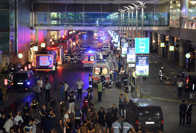 Medics and security members work at the entrance of the Ataturk Airport after explosions in Istanbul, Tuesday, June 28, 2016. Two explosions have rocked Istanbul's Ataturk airport, killing several people and wounding others, Turkey's justice minister and another official said Tuesday. A Turkish official says two attackers have blown themselves up at the airport after police fire at them. The official said the attackers detonated the explosives at the entrance of the international terminal before entering the x-ray security check. (Photo by IHA via AP Photo)