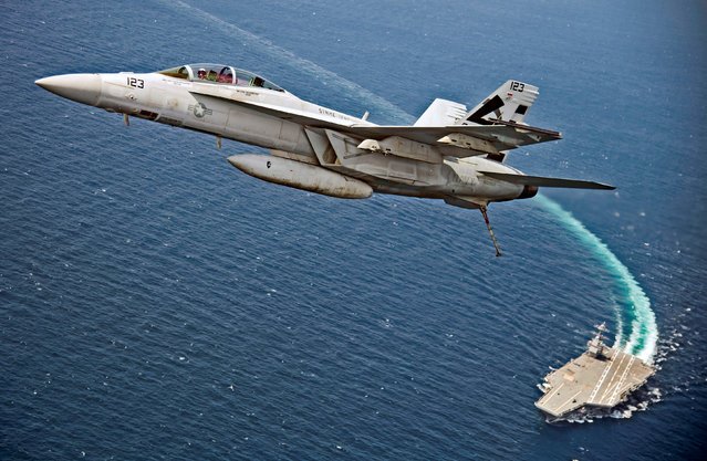 An F/A-18F Super Hornet jet flies over the USS Gerald R. Ford as the U.S. Navy aircraft carrier tests its EMALS magnetic launching system, which replaces the steam catapult, and new AAG arrested landing system in the Atlantic Ocean July 28, 2017. (Photo by Erik Hildebrandt/Reuters/U.S. Navy)