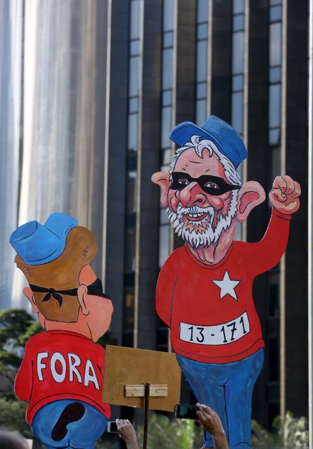 Demonstrators take photos of cardboard figures of former President Luiz Inacio Lula da Silva (R) and President Dilma Rousseff during a protest against Rousseff, part of nationwide protests calling for her impeachment, at Paulista Avenue in Sao Paulo's financial centre, Brazil, August 16, 2015. (Photo by Paulo Whitaker/Reuters)
