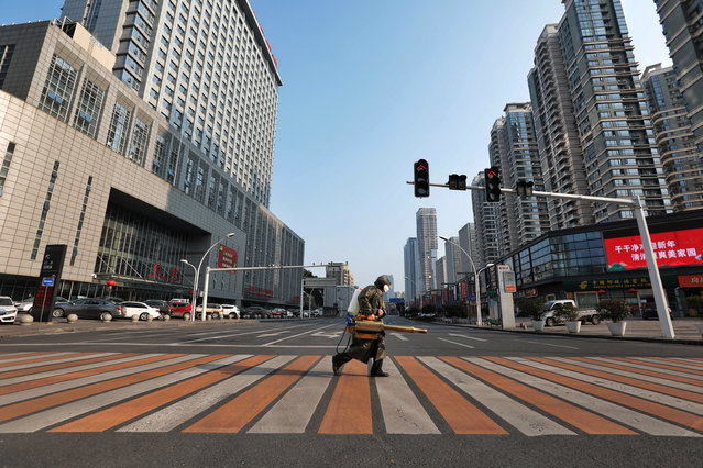 A worker with sanitizing equipment crosses the road in front of a hospital in Yichang city of Hubei, the province hit hardest by the novel coronavirus outbreak, China on February 12, 2020. (Photo by Reuters/China Daily)