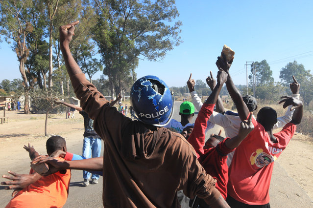 A rioter wearing a police helmet taken from a police officer joins angry protestors in Harare, Monday, July, 4, 2016. (Photo by Tsvangirayi Mukwazhi/AP Photo)