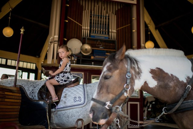 A girl rides a pony at the 1st Vienna Pony Carousel at the Prater amusement park in Vienna, Austria, 07 July 2016. The traditional merry-go-round closes it's doors due to concerns of animal rights after 129 years in business. (Photo by Christian Bruna/EPA)