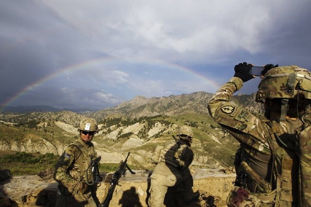 A paratrooper from Chosen Company of the 3rd Battalion (Airborne), 509th Infantry photographs a rainbow towards the end of a helicopter assault mission to improve their biological database, near the town of Ahmad Khel in Afghanistan's Paktiya Province July 16, 2012. Picture taken July 16, 2012. (Photo by Lucas Jackson/Reuters)