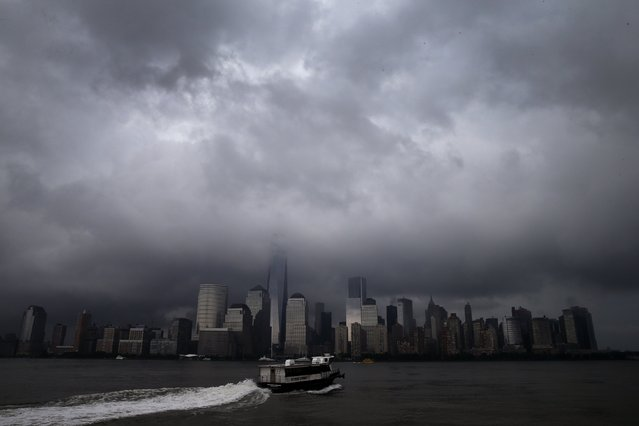 A ferry leaves Jersey City, New Jersey as it heads across the Hudson River towards lower Manhattan and New York City as a heavy thunderstorm passes over the area July 15, 2014. According to local reports severe thunderstorm and flash flooding warnings were issued for a second straight day as a powerful series of storms affected much of the northeast U.S. (Photo by Mike Segar/Reuters)