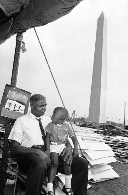 Roosevelt Nesmith of Camden, N.J., talks to his three-year-old son, Roosevelt Noel, about the August 28 civil rights March on Washington, August 27, 1963. Between the father and son, and the Washington Monument, is a stack of signs which the marchers, estimated to be more than 100,000, will carry in the demonstration. (Photo by AP Photo)