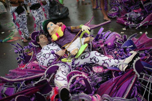 A samba school dancer rests after a carnival parade at the Sambadrome in Rio de Janeiro, Brazil, early Monday March 7, 2011. (Photo by Rodrigo Abd/AP Photo)