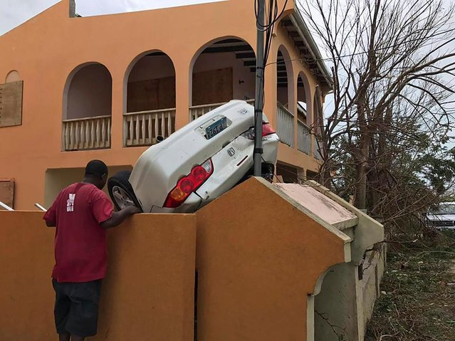 In this Wednesday, September 6, 2017 photo, a man looks at a vehicle turned upside down by winds brought on by Hurricane Irma in the British overseas territory of Anguilla. Irma scraped Cuba's northern coast Friday on a course toward Florida, leaving in its wake a ravaged string of Caribbean resort islands strewn with splintered lumber, corrugated metal and broken concrete. (Photo by Garson Kelsick via AP Photo)