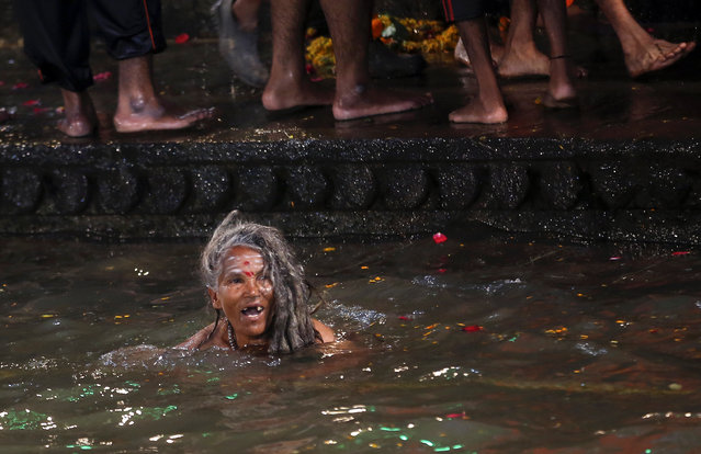 A Hindu holy woman bathes in the Godavari River during Kumbh Mela, or Pitcher Festival, at Trimbakeshwar in Nasik, India, Saturday, August 29, 2015. (Photo by Rajanish Kakade/AP Photo)