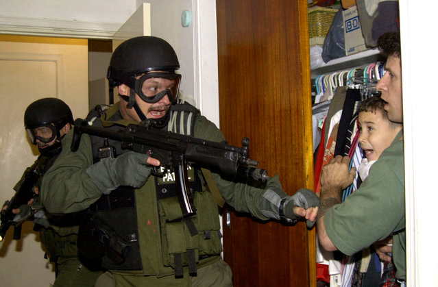 In this third of seven sequential photos, Elian Gonzalez is held in a closet by Donato Dalrymple, one of the two men who rescued the boy from the ocean, right, as government officials search the home of Lazaro Gonzalez for the young boy, early morning, April 22, 2000, in Miami, Florida. Armed federal agents seized Elian Gonzalez from the home of his Miami relatives before dawn, firing tear gas into an angry crowd as they left the scene with the weeping 6-year-old boy. This photo won the Prize in 2001. (Photo by Alan Diaz/AP Photo)