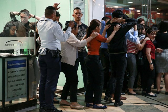 Archie Paray, a gunman and former security guard, surrenders and releases dozens of hostages outside a mall in San Juan, Metro Manila, Philippines, March 2, 2020. (Photo by Eloisa Lopez/Reuters)