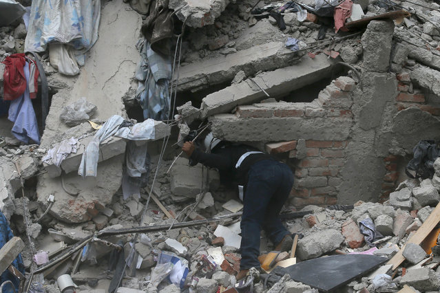 A construction worker searches a building that collapsed after an earthquake, in the Roma neighborhood of Mexico City, Tuesday, September 19, 2017. A magnitude 7.1 earthquake has rocked central Mexico, killing at least 55 people as buildings collapsed in plumes of dust and thousands fled into the streets in panic. (Photo by Eduardo Verdugo/AP Photo)