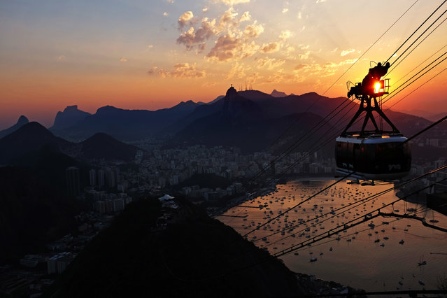 A cable car ascends to the top of Sugarloaf Mountain as the sun sets next to the Christ the Redeemer statue during the 2016 Summer Olympics in Rio de Janeiro, Brazil, Wednesday, August 17, 2016. (Photo by David Goldman/AP Photo)
