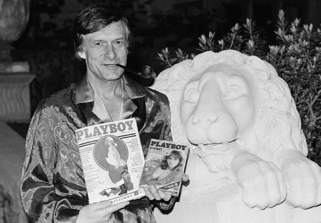 Playboy magazine publisher Hugh Hefner holds a copy of the magazine and a video cassette from the Playboy Channel, an all-night cable television venture Playboy Enterprises has undertaken, during an interview at the Playboy mansion in the Holmby Hills, November 29, 1982, Los Angeles, Calif. (Photo by Nick Ut/AP Photo)