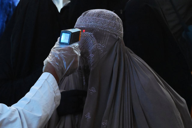 A health official checks the body temperature of a burqa-clad woman passenger amid concerns over the spread of the COVID-19 novel coronavirus at the Lahore Railway station in Lahore on March 19, 2020. (Photo by Arif Ali/AFP Photo)