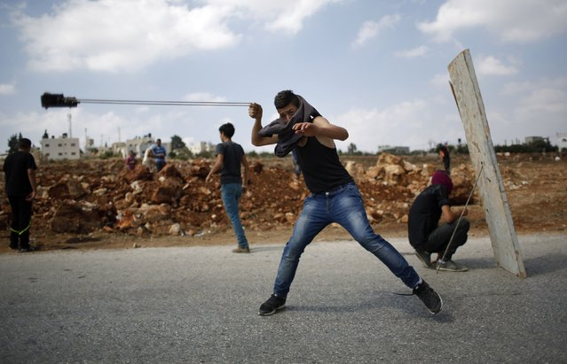 A Palestinian protester uses a sling shot to hurl a stone at Israeli troops during clashes at a weekly protest against Jewish settlements, in the West Bank village of Nabi Saleh, near Ramallah, September 5, 2014. (Photo by Mohamad Torokman/Reuters)