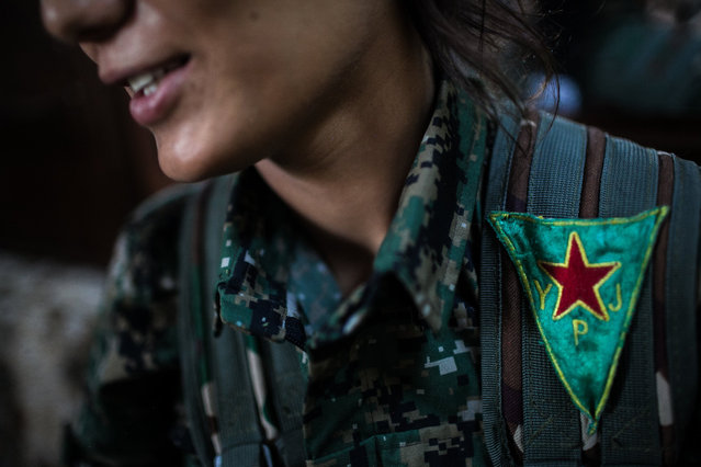 YPJ soldier, Amara, wears a red, yellow and green patch, the official flag of the YPJ, on her uniform near Girke Lege, Roshava, Syria on August 18, 2014. The colors of red, yellow and green have become Rojava's designated colors of patriotism – scarves, flags and posters are popular among the citizens who have embraced the YPJ as their official miliary. (Photo by Erin Trieb/NBC News)