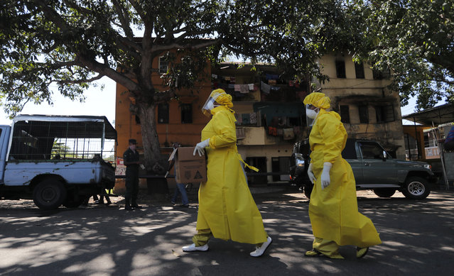 Sri Lankan health officials arrive to collect swab specimen from the suspected COVID-19 cases in a residential neighborhood during lockdown in Colombo, Sri Lanka, Thursday, April 16, 2020. Sri Lankan authorities claim they have largely managed to prevent community spreading through proper identification and isolation of people who came into contact with COVID-19 patients. (Photo by Eranga Jayawardena/AP Photo)