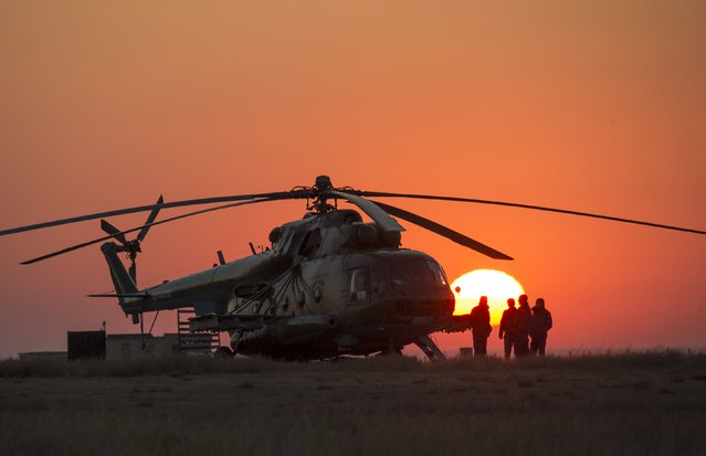 Ground support personnel are seen waiting to take off in their helicopter to support the Soyuz TMA-12M spacecraft, landing with International Space Station (ISS) crew members NASA astronaut Steve Swanson and Russian cosmonauts Alexander Skvortsov and Oleg Artemyev, at Dzhezkazgan September 11, 2014. (Photo by Bill Ingalls/Reuters/NASA)