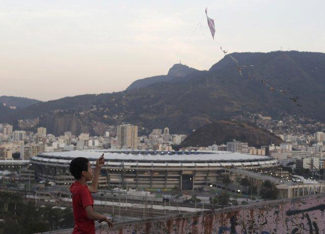 2016 Rio Olympics, Opening ceremony, Maracana, Rio de Janeiro, Brazil on August 5, 2016. A boy flies a kite in the Mangueira favela, or slum, overlooking the Maracana stadium. (Photo by Ricardo Moraes/Reuters)