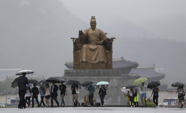 People hold umbrellas against the rain near the statue of the Chosun Dynasty's King Sejong, which has a height of 6.2 meter and weighs 20 ton, in downtown Seoul, South Korea, Monday, July 13, 2015. (Photo by Lee Jin-man/AP Photo)