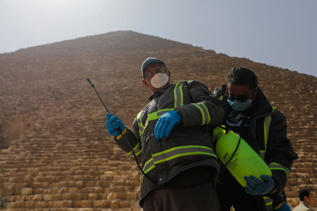 Members of the medical team prepare to spray disinfectant as a precautionary move amid concerns over the coronavirus disease (COVID-19) outbreak at the Great Pyramids, Giza, on the outskirts of Cairo, Egypt, March 25, 2020. (Photo by Amr Abdallah Dalsh/Reuters)