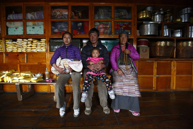 Nima Doma Sherpa, 25, whose husband Lakpa Sherpa, 26, died in the avalanche on April 18 2014, holds her daughter Pasang Choti Sherpa as she poses for a photograph with her father-in-law Tenzing Sherpa, 56, and mother-in-law Chamchi Phuti Sherpa, 55, inside their house in Khumjung in Solukhumbu District May 8, 2014. (Photo by Navesh Chitrakar/Reuters)