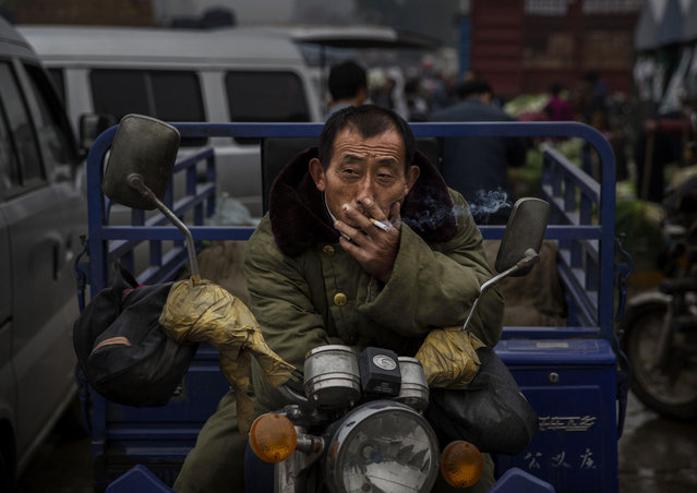 A Chinese laborer smokes a cigarette at a local market on September 26, 2014 in Beijing, China. China is challenged to ensure its food supply keeps pace with its population as more farmers leave the agricultural work force for jobs in the cities. Diets and lifestyles have also been altered by the rising affluence of China's growing middle class and its increasing demand for meat. (Photo by Kevin Frayer/Getty Images)