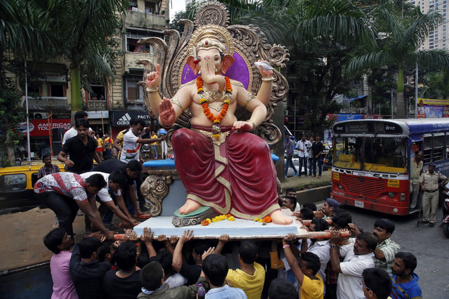 Devotees carry an idol of elephant headed Hindu god Ganesha from a workshop to a worship venue ahead of the Ganesh Chaturthi festival in Mumbai, India, Sunday, September 13, 2015. After worshipping during the ten day long festival, the idol will be immersed in the Arabian Sea. (Photo by Rajanish Kakade/AP Photo)